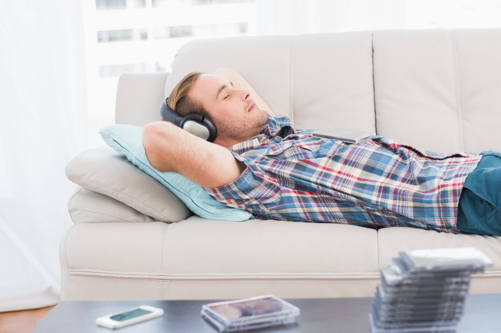 Man napping on sofa with music at home in the living room