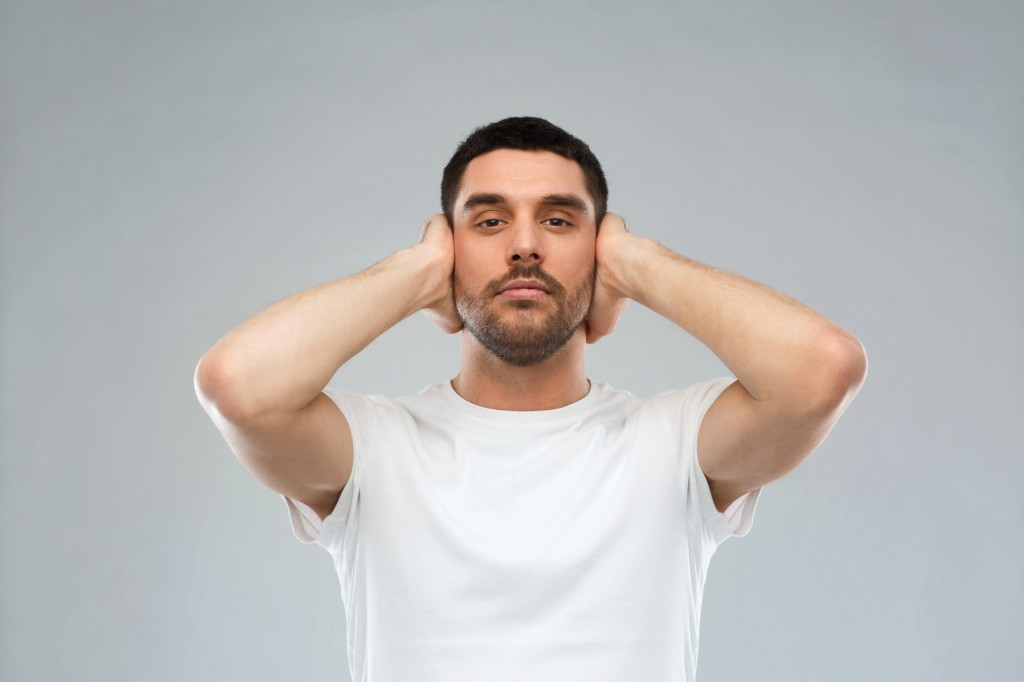 latin man covering his ears with hand palms