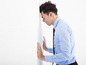 depressed young business man  leaning at the wall in office